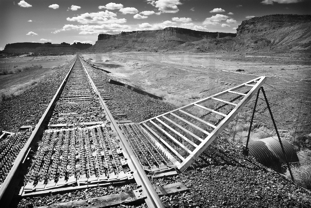 train tracks with cattle guard disappearing into the desert landscape, moab, southeastern utah, contrast the vast desert landscape