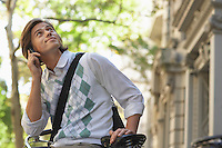Man sitting on bicycle talking on mobile phone and looking up