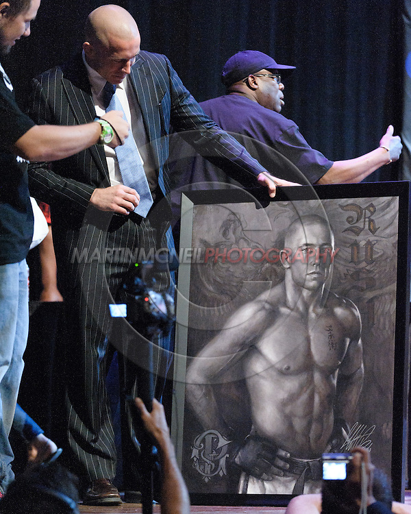 LAS VEGAS, NEVADA, JULY 9, 2009: UFC welterweight champion Georges St. Pierre (left) displays a portrait painted by artist Brian Fox (not pictured) after the pre-fight press conference for UFC 100 inside the House of Blues in Las Vegas, Nevada