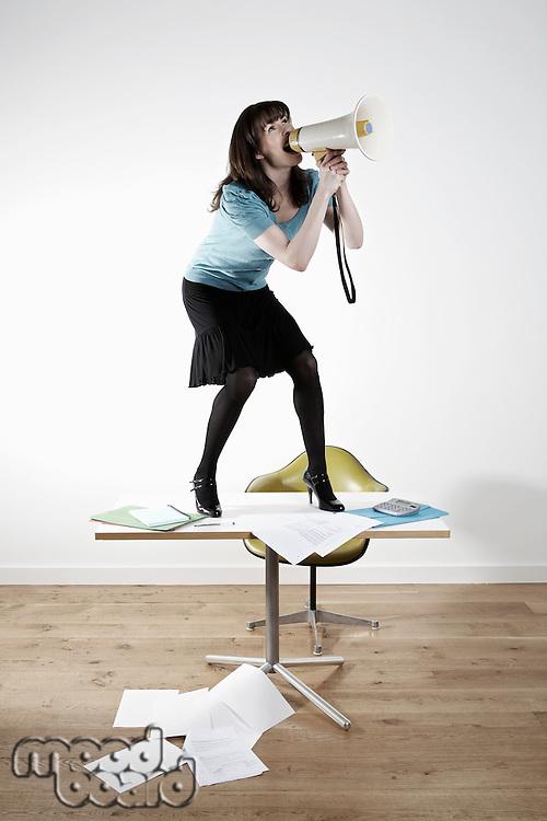 Woman standing on desk shouting through megaphone