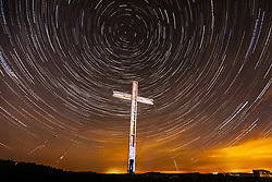 © Licensed to London News Pictures. 03/04/2017. Otley UK. Picture shows star trails over the Otley Chevin Cross in the early hours of this morning. The Cross that stands 30ft tall is placed on top of Otley Chevin every year to celebrate Easter & is made from salvaged timber from the bombed Arndale centre in Manchester. Picture is a composite of 90 images. Photo credit: Andrew McCaren/LNP