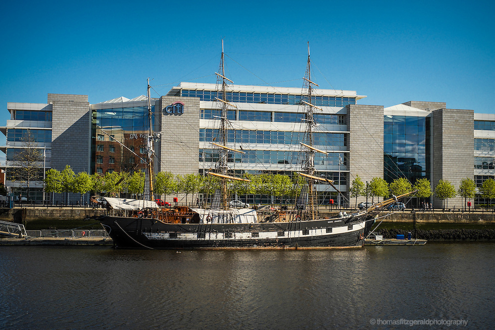 Dublin City, Ireland, May 2012: On the banks of the river Liffey in Dublin City, the Famous Tall Ship, the Jeanie Johnston lies moored in front of the Citi Building on the Dublin Quayside
