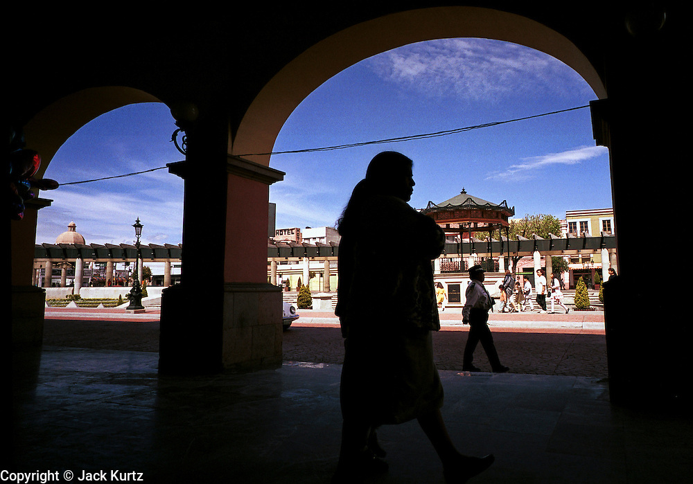 """JULY 19, 2000 - TOLUCA, MEXICO, MEXICO: A woman walks through the """"Portales""""  in the historic section of Toluca, Mexico, July 19, 2000. Life in Toluca, which is at an altitude of 8,500 feet with daily high temperatures in the 60's and 70's, does not prepare people who come to the US illegally for the brutal conditions of the Sonoran desert. Roberto Olvera Morales, of Toluca, died in the desert west of Douglas, AZ, when he tried to enter the US illegally with Maria Ordaz and her son. Morales was originally from Toluca, about 50 miles from Mexico City, where he worked with his mother at a taco stand. Morales was just one of the more than 150 Mexicans who died in the southwestern US trying to get into the United States without the proper immigration documents during the summer of 2000. Most died of heat exhaustion or thirst in the deserts that span the US/Mexico border, a region where daily high temperatures in the summer frequently soar to over 120 degrees Fahrenheit.  © Jack Kurtz  BORDER  IMMIGRANTS  POVERTY  HUMAN RIGHTS  FAMILY  WEATHER  FRONTERA  MIGRANTES  FAMILIA"""