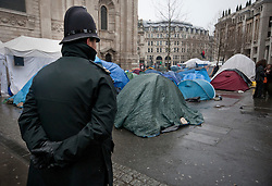 © licensed to London News Pictures. London, UK 18/01/12. A police officer is at the protest camp as Occupy London protesters wait the court decision of the camp's eviction request made by City of London Corporation in St Paul's. Photo credit: Tolga Akmen/LNP