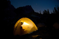 A tent glows from the headlamp of a camper in the Sawtooth Mountains, Idaho.