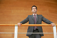 Businessman standing in office holding railing low angle view.