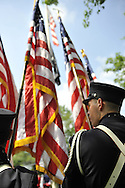 Firefighters band members holding American Flags during ceremony following Merrick Memorial Day Parade on Monday, May 28, 2012, on Long Island, New York, USA. America's war heroes are honored on this National Holiday.