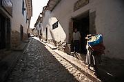 Indigenous woman walking up street Cusco, Peru