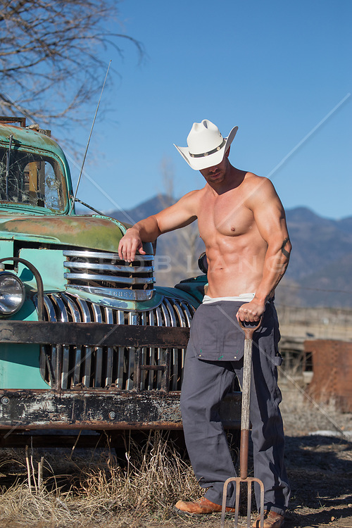 sexy man in a cowboy hat without a shirt holding a pitchfork.