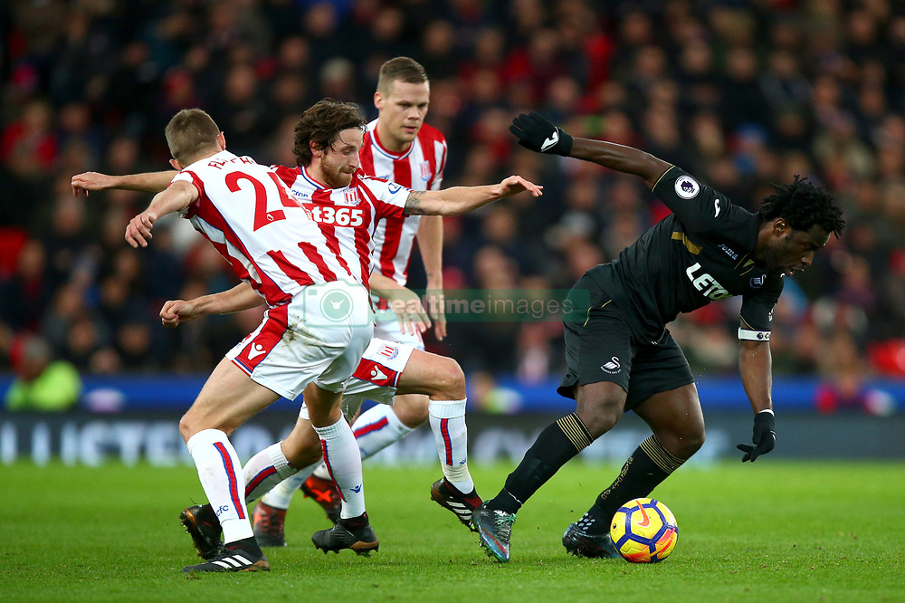 "Stoke City's Joe Allen challenges Swansea City's Wilfried Bony during the Premier League match at the Bet35 Stadium, Stoke. PRESS ASSOCIATION Photo Picture date: Saturday December 2, 2017. See PA story SOCCER Stoke. Photo credit should read: Dave Thompson/PA Wire. RESTRICTIONS: EDITORIAL USE ONLY No use with unauthorised audio, video, data, fixture lists, club/league logos or ""live"" services. Online in-match use limited to 75 images, no video emulation. No use in betting, games or single club/league/player publications"