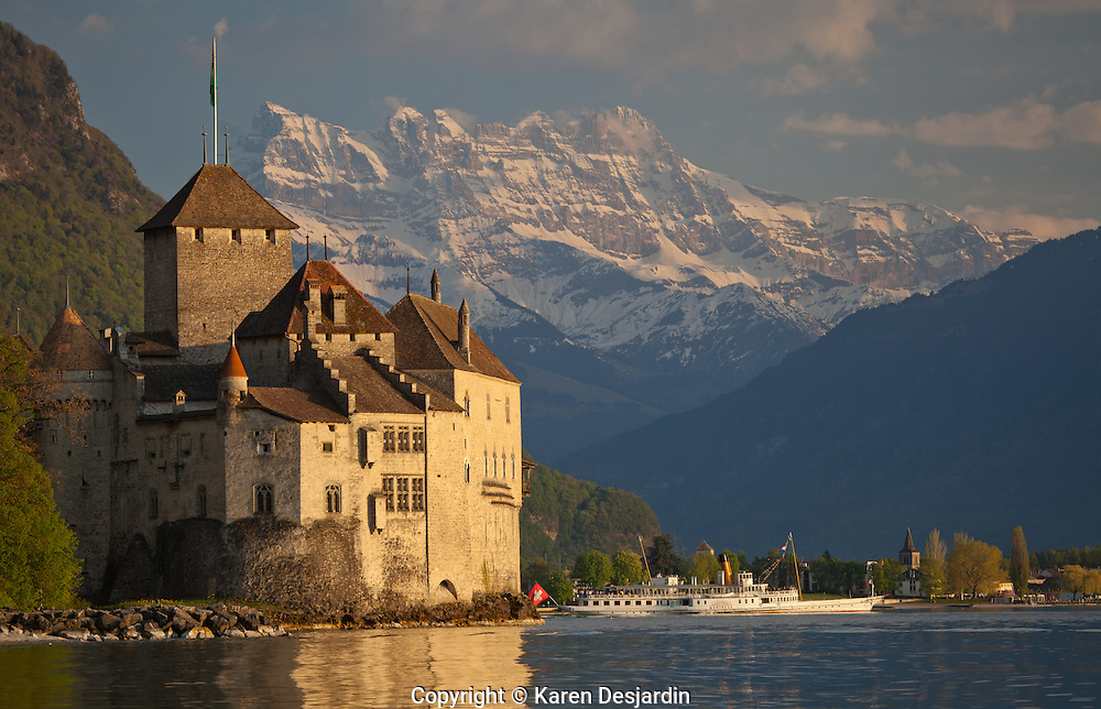 A cruise boat leaves the Chateau du Chillon on Lake Geneva (Lac Léman), near Montreux, Switzerland. The peaks of the Dents du Midi are visible in the background. The castle of Chillon was made popular by Lord Byron, who wrote the poem The Prisoner Of Chillon (1816) about François de Bonivard, a Genevois monk and politician who was imprisoned there from 1530 to 1536; Byron also carved his name on a pillar of the dungeon.