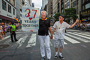 "A male couple walks down the parade route bearing a sign which reads ""37 years tgether."""