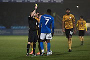 Referee C Pollard gives a yellow card to Macclesfield Town forward Arthur Gnahoua during the EFL Sky Bet League 2 match between Macclesfield Town and Crewe Alexandra at Moss Rose, Macclesfield, United Kingdom on 21 January 2020.