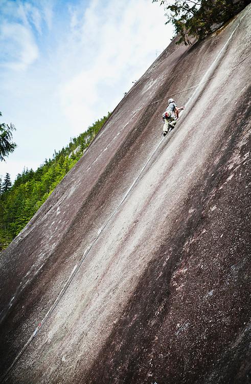 A man climbing Klahanie Crack (5.7) at Squamish BC, Canada.