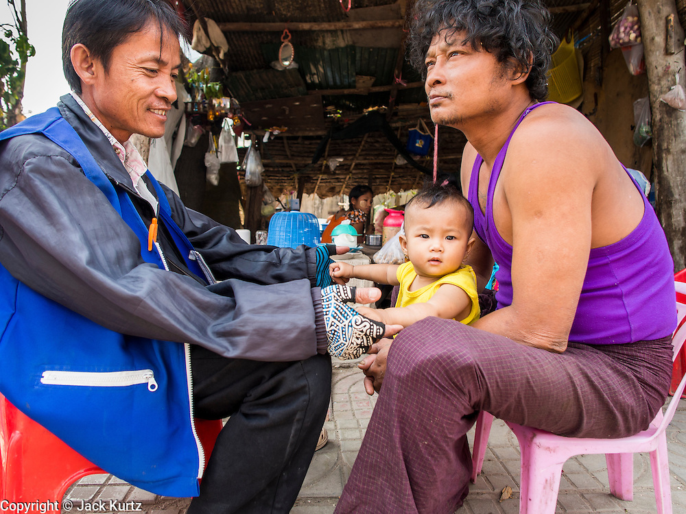 05 MARCH 2014 - MAE SOT, TAK, THAILAND: A man holds his son at a noodle stall in front of the Mae Tao Clinic in Mae Sot. The Mae Tao Clinic provides  healthcare to over 150,000 displaced Burmese per year and is the leading healthcare provider for Burmese along the Thai-Myanmar border. Reforms in Myanmar have alllowed NGOs to operate in Myanmar, as a result many NGOs are shifting resources to operations to Myanmar, leaving Burmese migrants and refugees in Thailand vulnerable.     PHOTO BY JACK KURTZ
