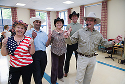 Group of older people line dancing,