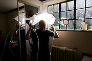 Priest puts on his Amice before morning Mass in Sacristy (Vestry) at St. Lawrence's Catholic church in Feltham, London.