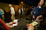Homeless day laborers queing outside Airin Labor Welfare Center for tickets to night shelters in the area.