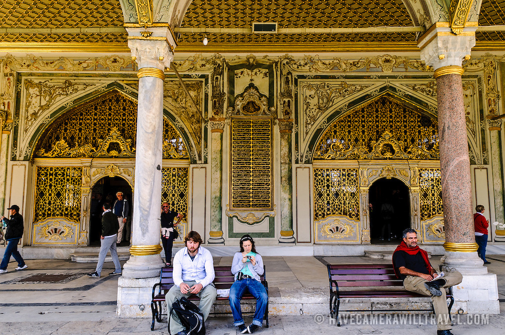 Tourists take a break outside the ornately decorated Imperial Chamber of the Topkapi Palace, the Ottoman palace in Istanbul's Sultanahmet district.
