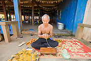 16 MARCH 2006 - KAMPONG CHAM, KAMPONG CHAM, CAMBODIA: A man hand rolls candles at Wat Hanchey, a pre Angkorian temple complex above the Mekong River near the city of Kampong Cham in central Cambodia. Photo by Jack Kurtz