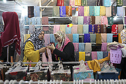 June 14, 2018 - Sungai Petani, Kedah, Malaysia - Two women are putting on hijabs in a store in Sungai Petani during Eid al-Fitr night eve, which marks the end of Ramadan..On June 15, 2018, Muslim throughout the world will celebrate Eid al-Fitr, after the holy month of Ramadan, in which Muslims refrain themselves from consuming food and drinks, smokes, and engaging in sexual activity from sunrise until sunset. (Credit Image: © Aizzat Nordin/SOPA Images via ZUMA Wire)