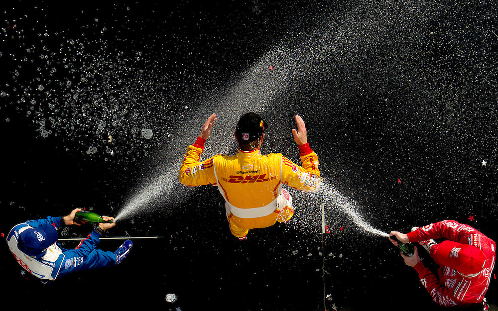 Ryan Hunter-Reay, driver of the #1 Andretti Autosport DHL Chevrolet gets sprayed with champagne by Helio Castroneves of Brazil, driver of the #3 AAA Insurance Team Penske Chevrolet (L) and Scott Dixon of New Zealand, driver of the #9 Target Chip Ganassi Racing Honda after winning the Honda Indy Grand Prix of Alabama at Barber Motorsports Park on April 7, 2013 in Birmingham, Alabama.