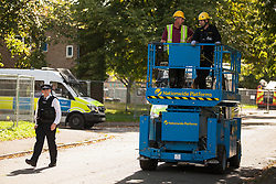London, UK. 23 September, 2015. A police officer escorts a cherry picker, or scissor lift, to be used by bailiffs to evict housing activists from the Sweets Way housing estate. A group of housing activists calling for better social housing provision in London occupied properties on the 142-home estate in Whetstone in order to try to prevent the eviction of the last resident on the estate and the planned demolition and redevelopment of the entire estate by Barnet Council and Annington Property Ltd.
