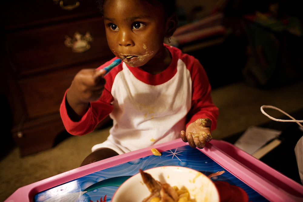 "Gabby, 2, eats a dinner of macaroni and cheese and fried chicken in the apartment she shares with her mother, Lettorea ""Lottie"" Clark, 25, in Albany, GA on Wednesday, October 22, 2008. Lottie and Gabby live off welfare after escaping an abusive relationship with Gabby's father."