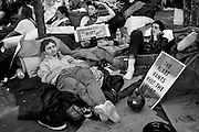 Twelve of 30. The 99% percenters demonstrating their anger with Wall Street's greed by occupying Zuccotti Park. Just off lower Broadway almost at the foot step of the new World Trade Center. This young man was one of many sleeping over at the park.