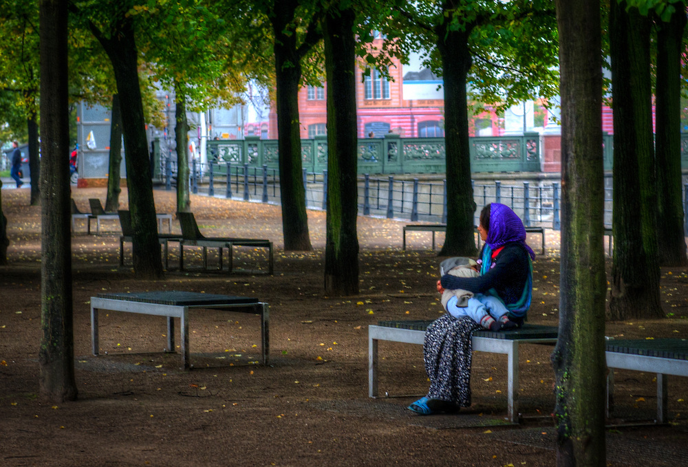 Woman with baby on park bench in Berlin