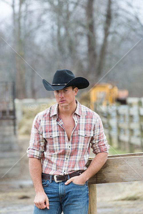 cowboy sitting on a ranch fence All American good looking cowboy on a ranch