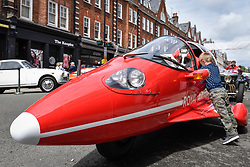 © Licensed to London News Pictures. 17/06/2018. LONDON, UK. A young boy examines a Pulse 'Jet Fighter' Autocycle finished in Red Arrows Red, complet with RAF Roundels ,at the 6th Annual Classic and Supercar Pageant held at St John's Wood High Street.  Traditionally taking place on Fathers' Day, the show brings together an eclectic mix of exotic and popular vehicles attracting visitors young and old and raises funds for the local charity, The St John's Hospice.  Photo credit: Stephen Chung/LNP