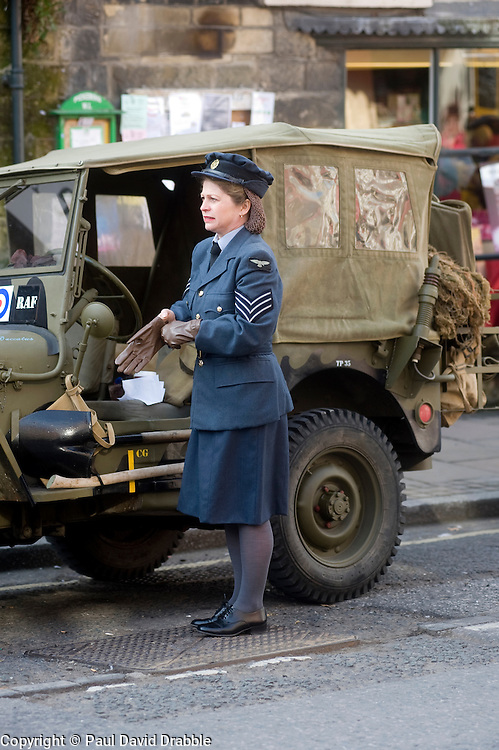 A reenactor portraying a Sergeant of the British Women's Auxiliary Air Force (WAAF) beside an RAF marked Willys Jeep at the Pickering 1940s war weekend 16th-18th October 2009 Image Copyright Paul David Drabble