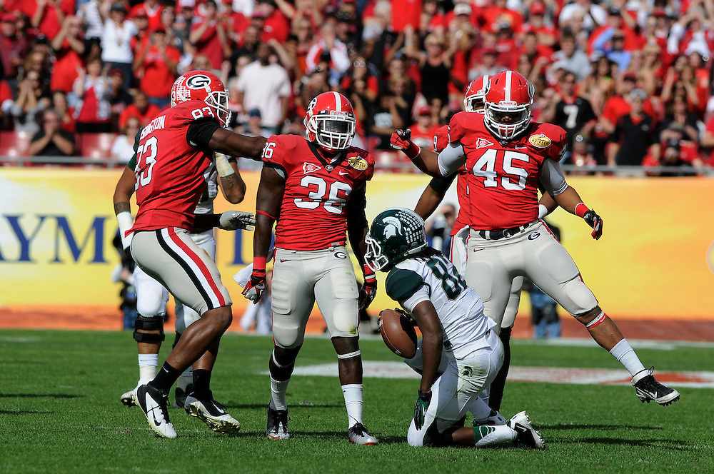 January 2, 2012: Cornelius Washington, Shawn Williams and Christian Robinson of Georgia celebrate after tackling Keshawn Martin of Michigan State during the NCAA football game between the Michigan State Spartans and the Georgia Bulldogs at the 2012 Outback Bowl at Raymond James Stadium in Tampa, Florida.