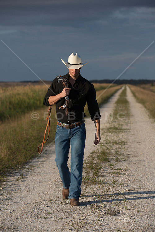 All American cowboy on a dirt road at sundown