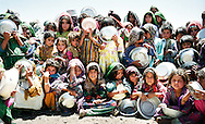 A group of young Afghan girls wait patiently in the mid-day heat to collect their ration of soup, available every other day. The boys queued separately, as is the custom in this devoutly Muslim area. <br /> <br /> Maslakh refugee camp, near Herat in Western Afghanistan