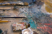 A detail image of an artist's palette and paints in various colors.