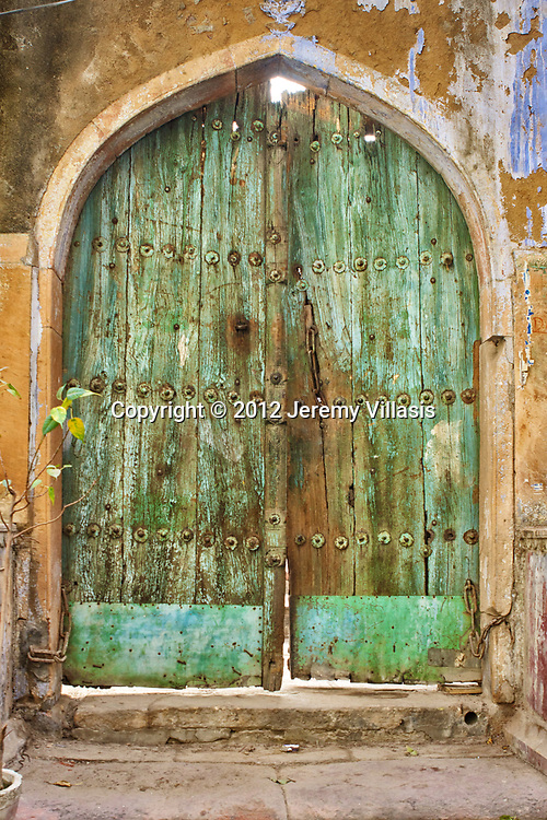Decaying wooden door in Naughara Gali, an alley in Chandni Chowk where nine colorful Jain havelis were built in the 18th century.