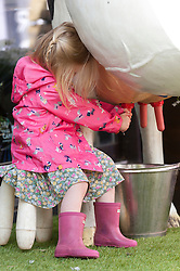 © Licensed to London News Pictures. 21/07/2015. Llanelwedd, UK. Three year old Awel Jones from Betws-y-coed practices her milkmaid skills on the second day of the show. The Royal Welsh Show is hailed as the largest & most prestigious event of it's kind in Europe. In excess of 200,000 visitors are expected this week over the four day show period - 2014 saw 237,694 visitors, 1,033 tradestands & a record 7,959 livestock exhibitors. The first ever show was at Aberystwyth in 1904 and attracted 442 livestock entries. Photo credit: Graham M. Lawrence/LNP