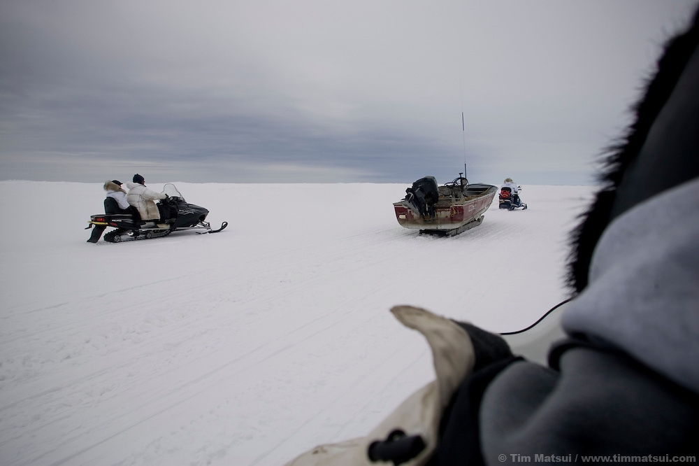 May 3, 2008 -- Kivalina, AK, U.S.A..Towing a boat to whaling camp, two miles out on the melting pack ice and 12 miles from the native village of Kivalina, Alaska. Kivalina is suing 20 oil companies for property damage related to global warming; the ocean pack ice forms later and melts earlier, leaving the town vulnerable to erosive winter storms and endangering their traditional subsistence lifestyle. (Photo by Tim Matsui)