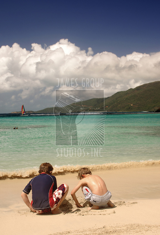 Two young boys building a sand castle on a tropical beach