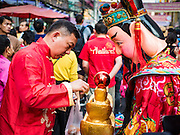 """08 FEBRUARY 2016 - BANGKOK, THAILAND: A man makes an offering to a Taoist deity during the Chinese New Year parade in Bangkok's Chinatown district during the celebration of the Lunar New Year. Chinese New Year is also called Lunar New Year or Tet (in Vietnamese communities). This year is the """"Year of the Monkey."""" Thailand has the largest overseas Chinese population in the world; about 14 percent of Thais are of Chinese ancestry and some Chinese holidays, especially Chinese New Year, are widely celebrated in Thailand.       PHOTO BY JACK KURTZ"""