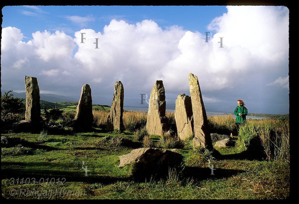 Woman admires 3000-year-old stone circle at Ardgroom once used as a calendar; Beara Peninsula, Ireland.