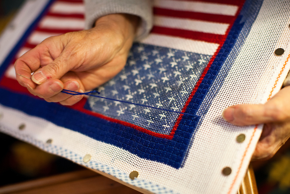 A woman sews an American flag on Tuesday, January 17, 2012 in Columbia, SC.