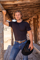 hot cowboy by a rustic cabin