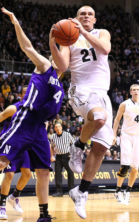Feb. 12, 2012; West Lafayette, IN, USA; Purdue Boilermakers guard/forward D.J. Byrd (21) puts the ball up as Northwestern Wildcats guard Alex Marcotullio (4) defends from behind at Mackey Arena. Purdue defeated Northwestern 87-77. Mandatory credit: Michael Hickey-US PRESSWIRE