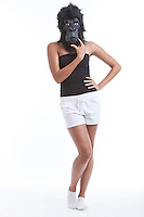 Portrait of young woman wearing gorilla mask with hand on hips against white background