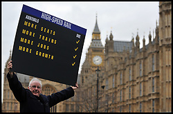 Pete Waterman, record producer and songwriter, holds up a High Speed Rail Arrivals card outside the House of commons in favour of the announcement  today that Phase one of high-speed rail line gets go-ahead, Tuesday January 10, 2012. Photo By Andrew Parsons/ i-Images