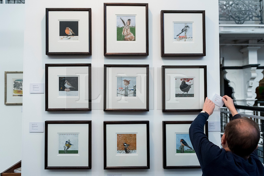 © Licensed to London News Pictures. 17/01/2017. London, UK.  Ewan Mundy, of Ewan Mundy Fine Art, applies labels to paintings on his stand at the preview of the 29th London Art Fair, the UK's premier fair for Modern British and contemporary art, taking place at the Business Design Centre in Islington from 18-22 January 2017, where 129 galleries from 18 different countries will be presenting their artworks. Photo credit : Stephen Chung/LNP