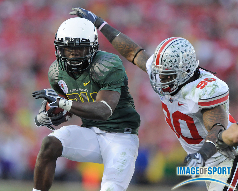 Jan 1, 2010; Pasadena, CA, USA; Oregon Ducks running back Kenjon Barner (24) tries to elude Ohio State Buckeyes defensive end Thaddeus Gibson (90) in the 2010 Rose Bowl at the Rose Bowl. Ohio State defeated Oregon 26-17.